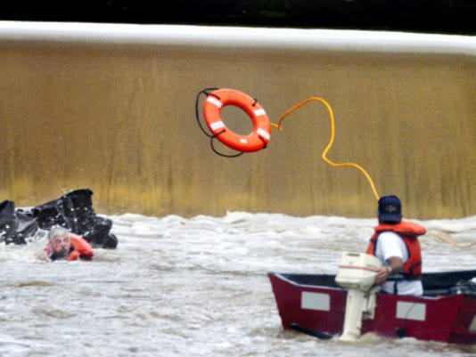 A volunteer firefighter from East Berlin Search and Rescue Company No. 11 throws a life preserver to another firefighter at the base of the Conewago Creek Dam near Route 234 in East Berlin in July 2005. The man in the water and another firefighter were on a hovercraft that capsized while they were searching for two missing men who had gone over a low-head dam on the creek and were later found dead.