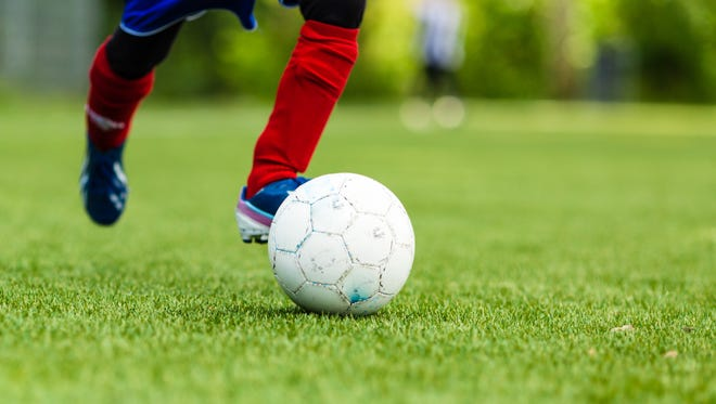 Picture of young soccer player dribbling with a soccer ball.