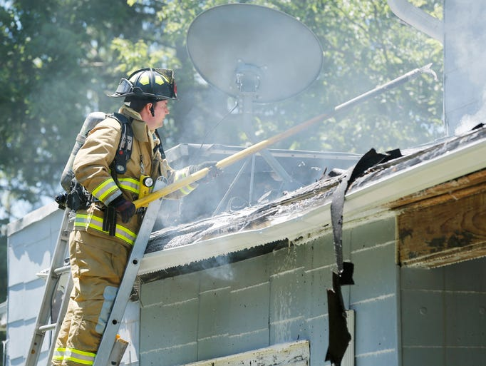 A firefighter works to reach a hot spot in the roof during a house fire Friday, June 13, 2014, at 103 E. Oak Street in West Lafayette. Homeowner Michael Poling said he accidentally started the fire when he was removing paint with a heat gun. There were no injuries.