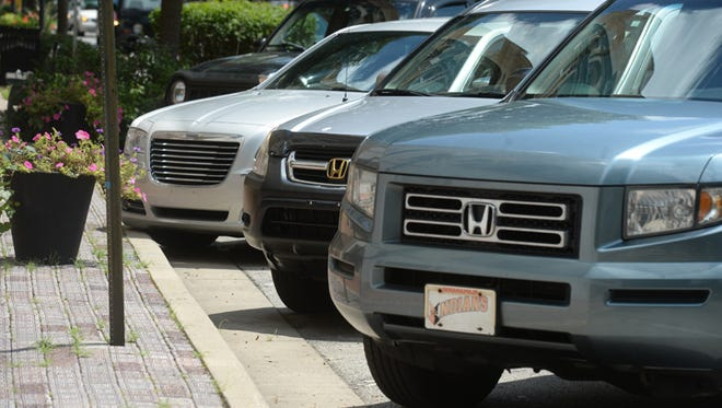 Cars in angle parking spots along East Main Street Tuesday, July 21, 2015, in Richmond.