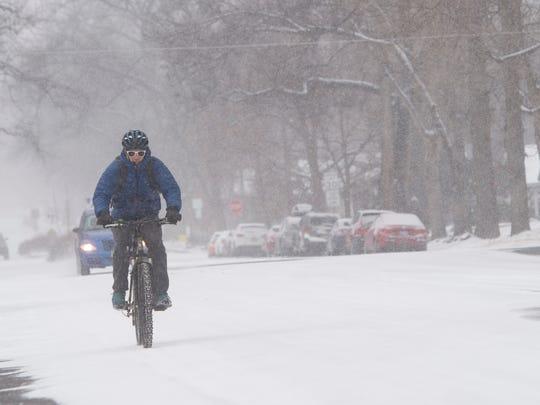 A man navigates snow-packed roads on his bicycle on