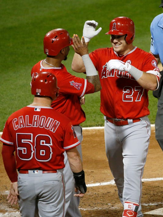 Los Angeles Angels' Mike Trout (27) celebrates his three-run home run off Chicago White Sox starting pitcher Chris Volstad with Martin Maldonado and Kole Calhoun (56) during the second inning of a baseball game Tuesday, Sept. 26, 2017, in Chicago. (AP Photo/Charles Rex Arbogast)