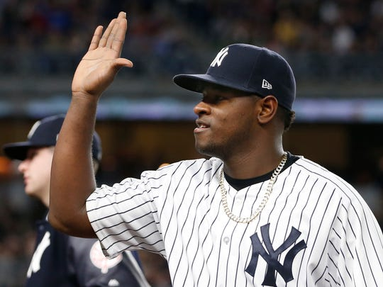 New York Yankees starting pitcher Luis Severino reacts as teammates come out to greet him after he pitched eight innings in the Yankees 3-0 shutout of the Kansas City Royals in a baseball game at Yankee Stadium in New York, Wednesday, May 24, 2017.