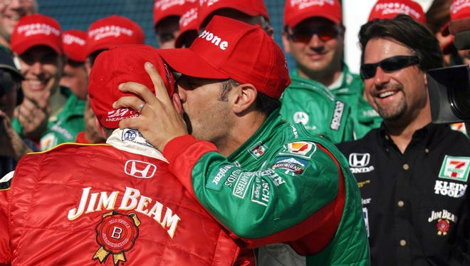 Tony Kanaan center of Brazil plants a kiss on the cheek of pole-sitter Dan Wheldon of Britain during a victory lane ceremony following Kanaan's win at the Copper World Indy 200 Sunday March 21 2004 at Phoenix International Raceway in Avondale Ariz. At right is Andretti Green Racing  owner Michael Andretti.(AP Photo/Roy Dabner)