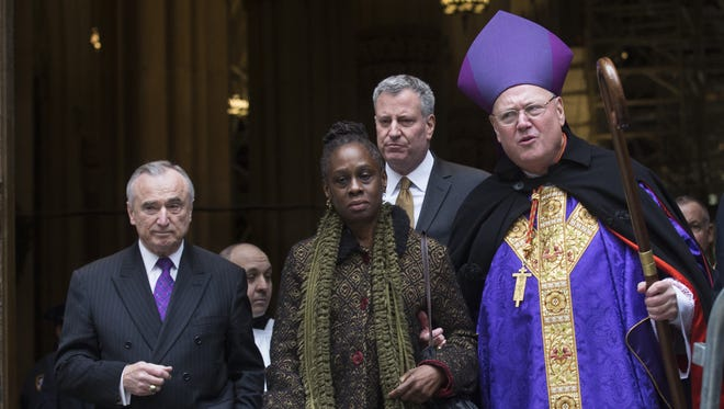 From left, NYPD Commissioner Bill Bratton, New York City first lady Chirlane McCray, New York City Mayor Bill de Blasio, and Catholic Cardinal Timothy Dolan leave St. Patrick's Cathedral following a Mass, Sunday, Dec. 21, 2014, in New York.