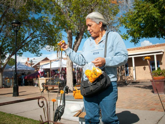Priscilla Perez builds a shrine to her family on Mesilla Plaza during the Dia De Los Muertos celebrations.