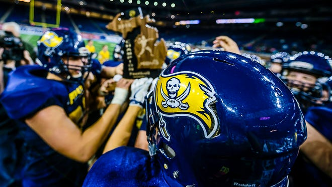 The Pewamo-Westphalia football team holds the Division 7 state championship trophy after their defeat of Detroit Loyola on Saturday, November 26, 2016, at Ford Field in Detroit.