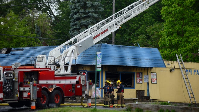 Crews work the scene of a fire at the M-9 Party Store in Lansing on Friday, June 9, 2017.