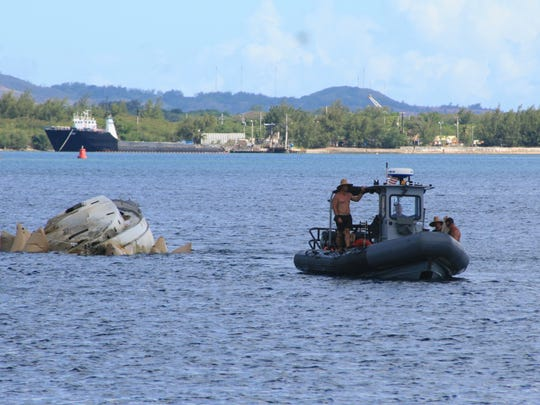 Members of Mobile Dive Salvage Unit 1 in Guam participating in the Western Pacific Naval Symposium Diving Exercises tow a derelict 42-foot sailboat across Apra Harbor on June 15.