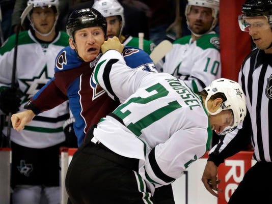 Colorado Avalanche center Cody McLeod, left, fights with Dallas Stars' Antoine Roussel (21) in the first period of an NHL hockey game Saturday, Oct. 10, 2015, in Denver. (AP Photo/Joe Mahoney)