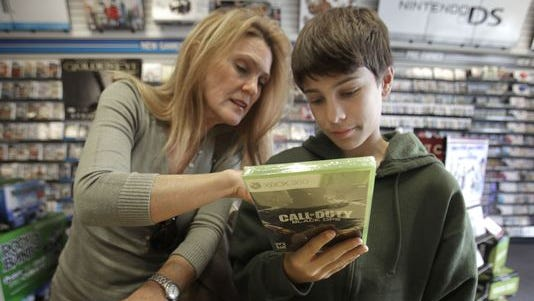 """Augustine Sewell, 13, and his mother, Patricia Sewell, look over the """"Call of Duty: Black Ops"""" video game they purchased in Sacramento in 2010."""