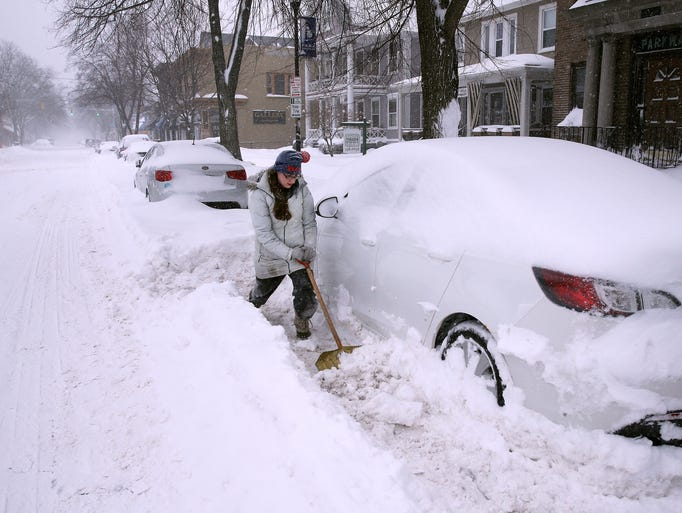 Kelly Pierce  tries to shovel out her car which was