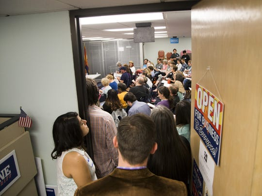 People peer into the packed Arizona Democratic Party