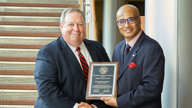 Holy Family Memorial CEO Mark Herzog (left) receives a plaque from Kim Byas Sr. from the American Hospital Association.