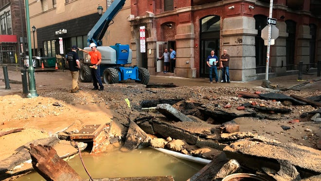 Philadelphia Water Department personal work in Philadelphia where a water main break occurred early Tuesday, July 3, 2018. The break happened before 4 a.m. Tuesday, and a number of center city streets have been closed. (Jessica Griffin/The Philadelphia Inquirer via AP)
