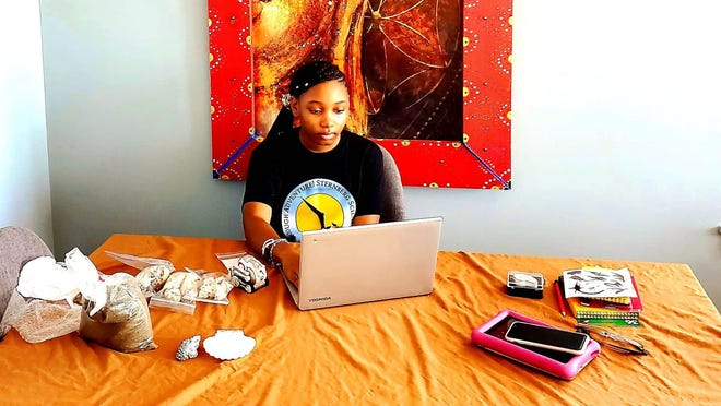 Surrey Jones, a middle school camper from Chicago, works at her family's dining room table, surrounded by materials she received in her camp kit box for the Ancient Seas camp.