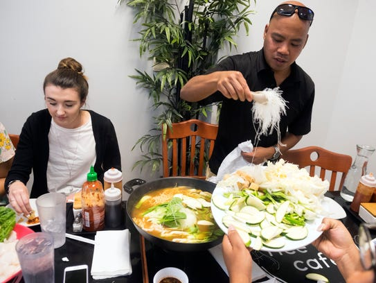 Joe Consumo loads a hot pot with noodles and vegetables for cooking. Consumo experienced hot pot meals in his travels and talked the owner of Sticky Rice Cafe into offering it to customers.
