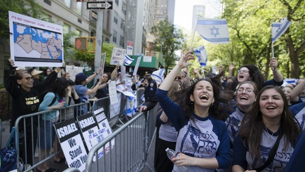 Marchers cheer as they pass along a barricade separating