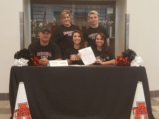 Aztec's Tori Riddick, center, signed a letter of intent to cheer for Bethel College on May 9 at Lillywhite Gym in Aztec.