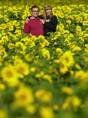 John and Jan Frederick among their field of black oil sunflowers, July 2001.