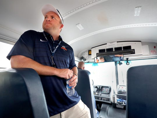 "Blackman coach Kit Hartsfield instructs players before leaving the school parking lot that ""this is not a fun trip,"" so they need to remain quiet on the bus."