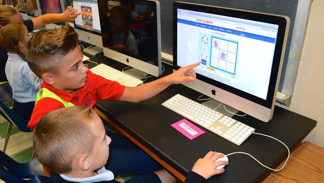 "D'Amani Almodovar, an eighth grader at Bishop Schad Regional School in Vineland, helps Logan Ferretti, a first grader, with the ""First in the Math"" program. For school information, call (856) 691-4490."