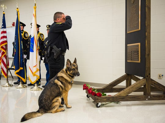 Chief Mike Woods with the McSherrystown Police Department salutes while placing a rose for a fallen K-9 with McSherrystown Police Department's seven year-old K-9 unit, Ozi, during the Adams County Fallen Officers Memorial service on Friday May 6, 2016 at the Adams County 911 Center.