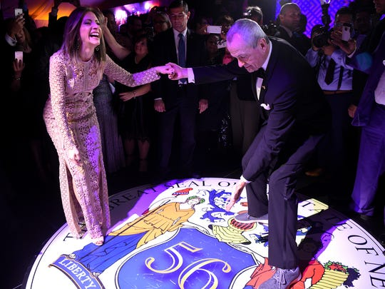 New Jersey's 56th Governor Phil Murphy and First Lady Tammy Murphy stop during their first dance while the governor points to the state seal of New Jersey projected on the dance floor at MetLife Stadium in East Rutherford on Tuesday, January 16, 2018.
