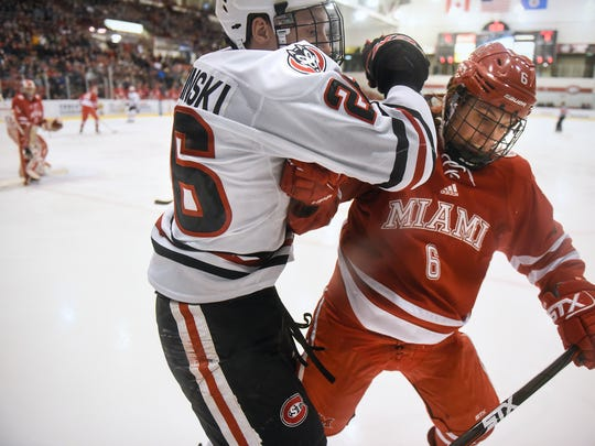 St. Cloud State's Easton Brodzinski and Miami's Alec Mahalak collide along the boards during the first period of the Friday, March 9, game at the Herb Brooks National Hockey Center in St. Cloud.
