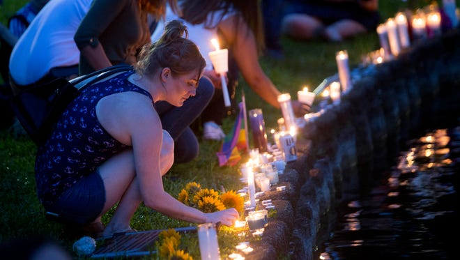 A woman places a candle Sunday at Lake Eola in Orlando during a vigil for those killed and injured in a mass shooting at the Pulse night club.