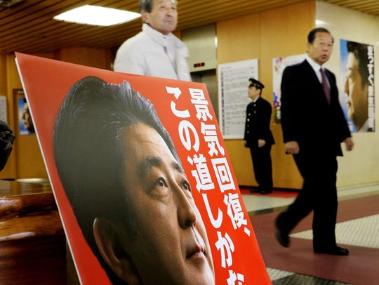 People walk past a poster of Japanese Prime Minister