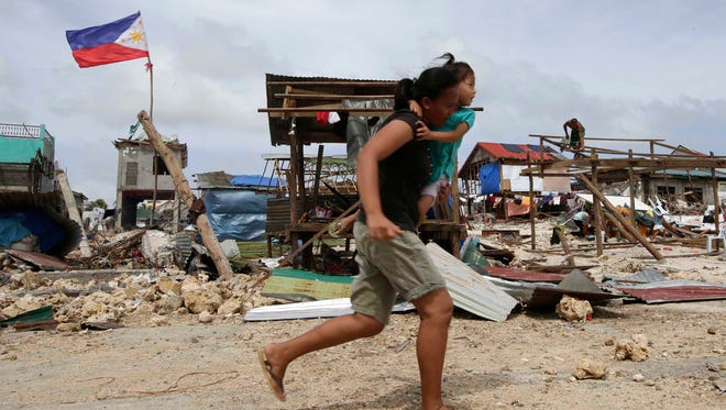 Residents walk past the debris as others rebuild their houses following the devastating typhoon that hit the Philippines Friday.