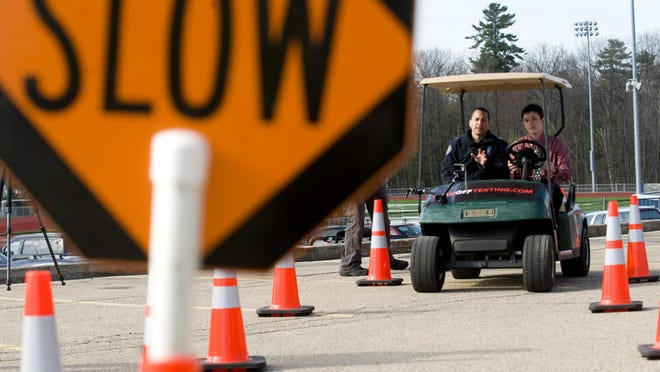 """Tomash Zentrich, 17, tries to text while driving a golf cart through an obstacle course at Burlington High School in 2010. The course is part of the """"Turn Off Texting"""" campaign, a partnership between the Dept. of Motor Vehicles and the Youth Safety Council of Vermont."""