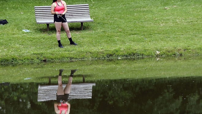 Hannah Hill fishes on Monday at the pond at Brookside West in Ashland.