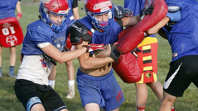 Mapleton running back Bryar Ramey protects the football from Corbin Clark (left) while running a drill during practice on Thursday at Mapleton High School.