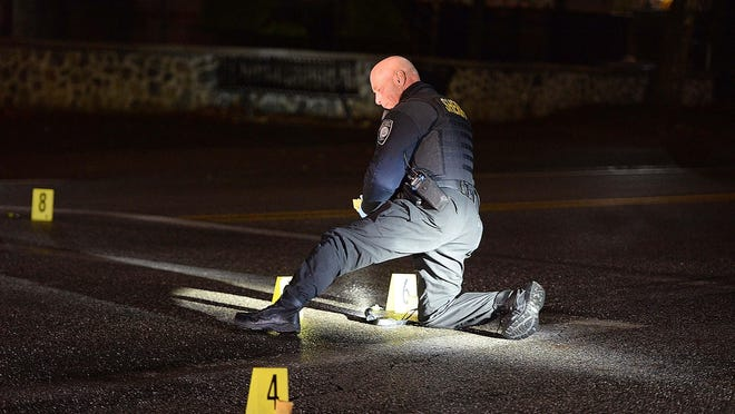 In a Jan. 14, 2020, file photo, a sheriff's deputy with the Plymouth County Bureau of Criminal Investigation takes photographs of shell casings.