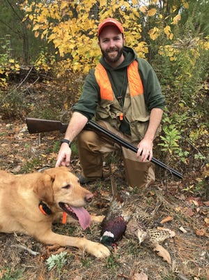 Tom White pauses with his best hunting buddy Sadie and a brace of pheasants.