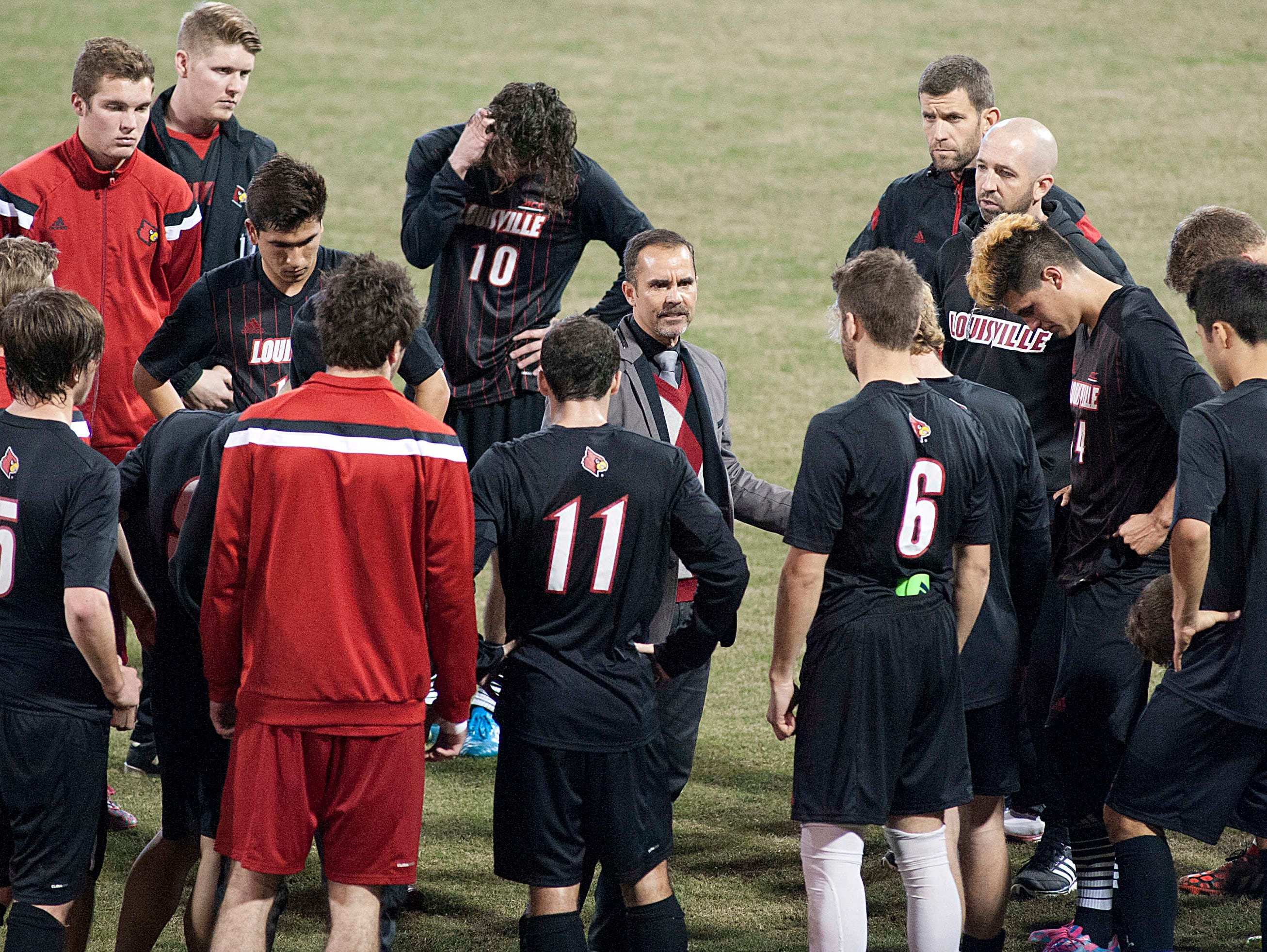 Louisville Cardinals' head soccer coach Ken Lolla, center, talks to his team following their 2-1 loss to UCMB. 30 November 2014