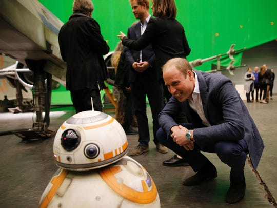 Prince William meets BB-8 droid as Prince Harry chats in background during a tour of the 'Star Wars' sets at Pinewood Studios west of London on April 19, 2016.