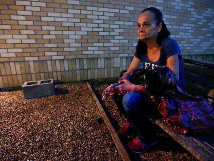Holding her dog Emily, Julie Starbuck, 51, smokes outside