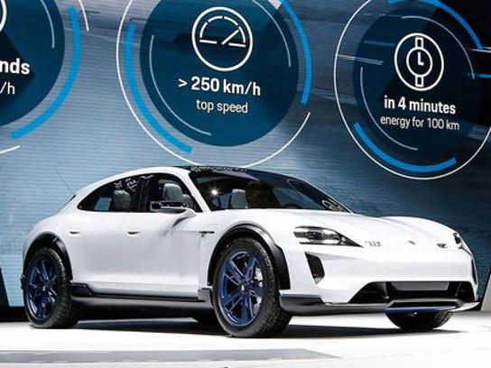 The Porsche Mission E Cross Turismo, a low-slung white SUV, on Porsche's show stand at the Geneva International Motor Show in March 2018.