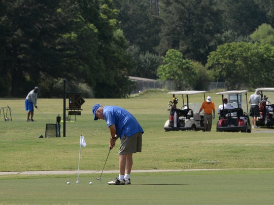 Burley Phillips works on his short game as several
