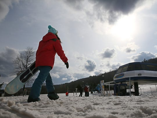 Christie Stanzione heads for a lift as snow clouds close in as she snowboards at Bristol Mountain.