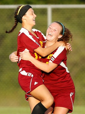 Jordan Nakaguchi, left, is congratulated by teammate Abigail Childers after her goal put the McCutcheon up 1-0 over Harrison in the first half Wednesday, August 31, 2016, in West Lafayette. McCutcheon defeated Harrison 3-2.