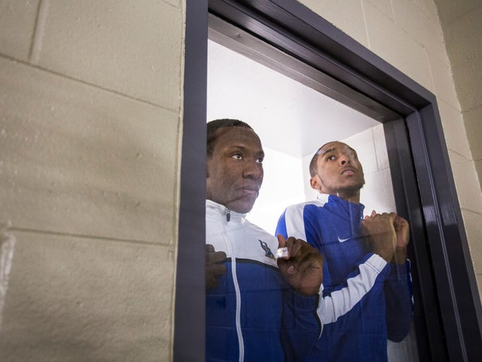 Delaware guards Devon Saddler, left, and Davon Usher, right, look through a window into the gym at the Carpenter Sports Complex before entering the watch party.