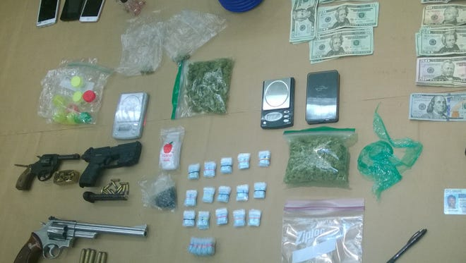 New Castle County police seized guns, heroin and other drugs from a vehicle and home in Bear on Sunday.