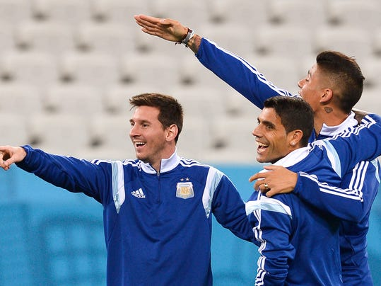 Argentina's Lionel Messi, left, gestures with teammates Marcos Rojo, right, and Augusto Fernandez, center, during an official training session the day before the World Cup semifinals soccer match between Netherlands and Argentina at the Itaquerao Stadium in Sao Paulo, Brazil, Tuesday, July 8, 2014. (AP Photo/Manu Fernandez)