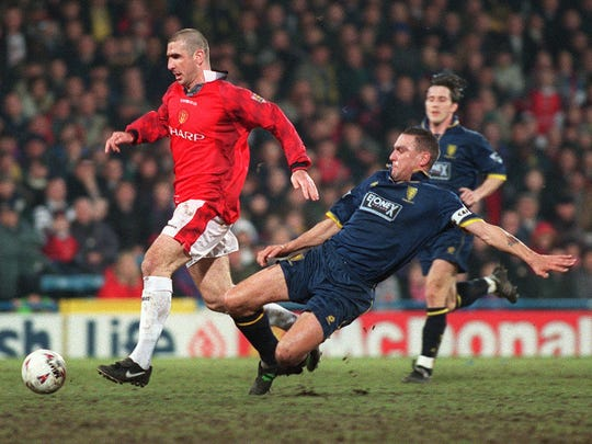 FILE - This is a Tuesday Feb. 4, 1997 file photo of  Wmbledon's Vinnie Jones, right,  as he challenges  Manchester United's Eric Cantona.