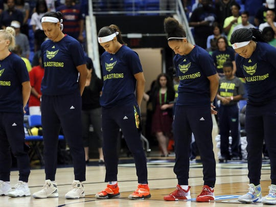 """The Dallas Wings' Erin Phillips (from left), Plenette Pierson, Skylar Diggins, Brianna Kiesel and Odyssey Sims bow their heads during a moment of silence before the July 17 game against the Minnesota Lynx in Arlington, Texas. The Wings wore shirts with the slogan """"Dallas Strong"""" in observance of recent events where five Dallas police officers lost their lives."""