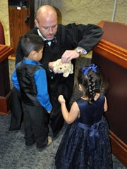 Judge Timothy McCoy gives children a stuffed animal.